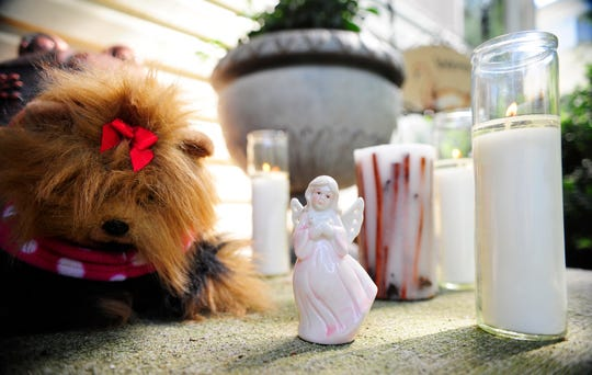 "In this file photo from June 8, 2012, lit candles, a stuffed animal and an angel statuette stand as a memorial for Cherylann ""Jen"" Dowell, who was found dead in her apartment on the 500 block of Cedar Village Drive in Manchester Township."