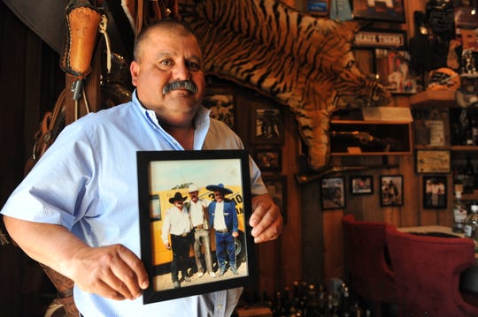 Salinas resident Ricky Cabrera poses with a framed photo, left to right,  of himself, Mexican singer Lalo Mora and Alfonso Cabrera, who is seen wearing the same charro suit donated to the Salinas Police Department. July 22, 2019.
