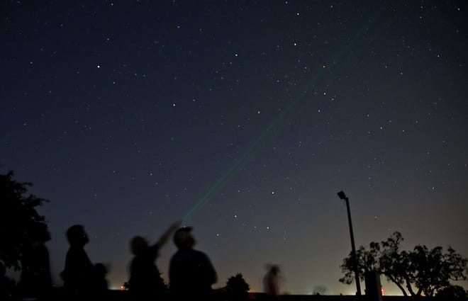 A green laser pointer is used by San Angelo Astronomy Association President Andy Oliver to teach people about constellations  at San Angelo State Park on Saturday, July 20, 2019.
