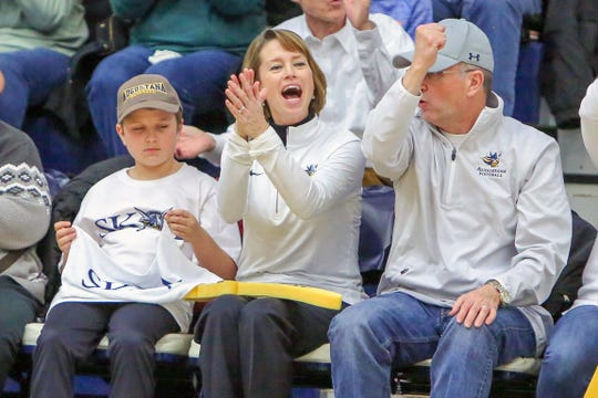 Augustana University president Stephanie Herseth Sandlin (center) cheers on the Vikings with her family. She is leading the school's planned transition to NCAA Division I status.