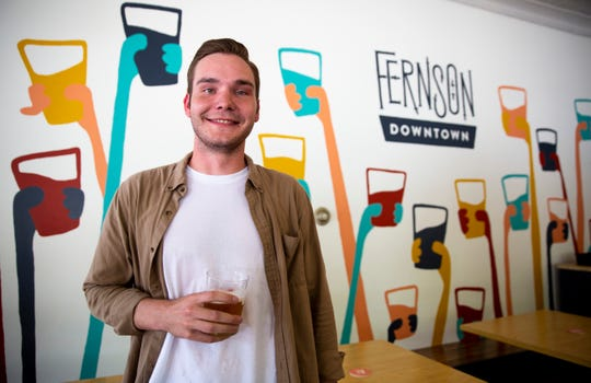 Evan Richards, marketing director of Fernson Brewing Company, speaks to the strategic marketing tools implemented in the downtown location, Wednesday, July 17. Richards designed the mural behind him with the intent of using this artwork as marketing tool for social media sites such as Instagram.