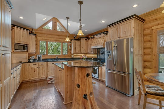 The log home's kitchen incorporates a tree that's native to the lot as a a wine display.