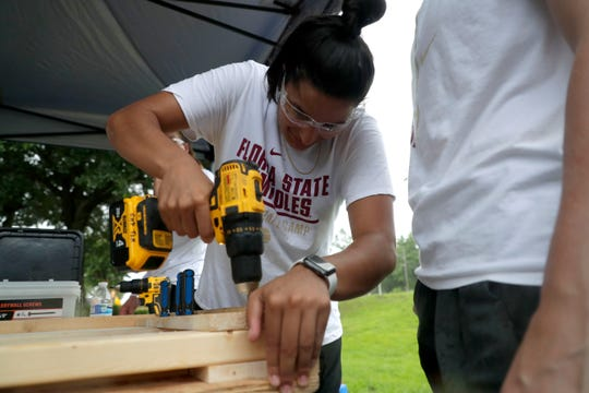 Izabela Nicoletti, a member of the Florida State women's basketball team, uses a drill to put together a headboard for a bunkbed for children in the Big Bend. FSU women's basketball teamed up with Texas Roadhouse and other volunteers to complete the project Tuesday, July 23, 2019.