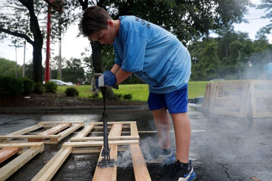 Mason Stafford, 11, brands the Sleep in Heavenly Peace logo to a headboard. FSU women's basketball teamed up with Texas Roadhouse and other volunteers to build bunkbeds for children in the Big Bend Tuesday, July 23, 2019.