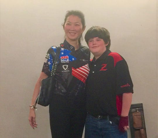 "World-renown player Jeanette ""Black Widow"" Lee poses with Trenton Rottman at the American Poolplayers Association Junior Championship in St. Louis."