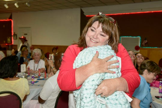 Darlene Perdue hugs the handcrafted chunky blanket that she won at the Ladies of Jewelia's All American Bingo benefit for HANDS of St. Lucie County, a Volunteers in Medicine Clinic. The blanket was made by Sydney Liebman.