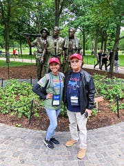 Kayla Williams, left, with veteran Leo Gonzalez stand in front of a statue in Washington, D.C., during a recent Southeast Florida Honor Flight trip there.