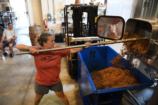 TCPalm entertainment reporter and columnist Laurie Blandford rakes the drained mash from a tank in the first phase of creating a batch of craft beer for one of the Press Journal beers for the Vero Beach Centennial on Monday, July 15, 2019, at the Walking Tree Brewery in Vero Beach.