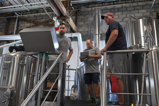 Mike Malone (from left), co-founder of  Walking Tree Brewery, monitors a control panel during the mash conversion process of brewing beer with TCPalm columnist Larry Reisman and photographer Patrick Dove, while brewing one of the Press Journal beers for the Vero Beach Centennial on Monday, July 15, 2019, at the brewery in Vero Beach.