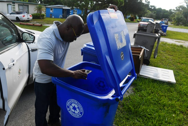 Indian River County's  aggressive crackdown on people who put non-recyclables in the blue recycling carts is starting to generate complaints from people whose recycling carts are left at the curb, uncollected. Here, Antowain Person, county landfill foreman, takes photos of a contaminated recycling bin while conducting a field audit. Those audits are continuing.