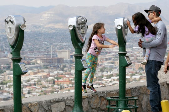 """""""Can you see me?"""" Valentina Herrera, 4, asked her younger sister, Dalary, 3, as she peered through a viewer at Scenic Drive on Tuesday, July 23, 2019, with her father, Armando Herrera, after a short rainfall cooled down El Paso, giving families a chance to enjoy the outdoors after days of high heat."""