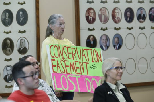 A sign calling for easement of Northwest El Paso land is held up at the El Paso City Council meeting on Tuesday, July 23.