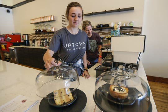 Employee Ella Schultz works July 17, 2019, at Uptown Coffee Company in Marshfield, Wis. Behind Schultz, co-owner Vicki Tracy prepares to make a cup of coffee.
