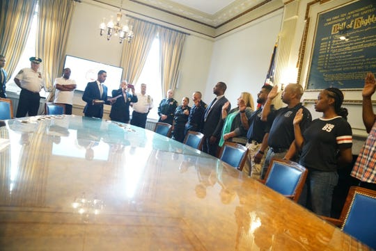 Richard Thomas, head of the table, swearing in new Mount Vernon detectives on July 18, 2019. To the right of Thomas are Lt. Marcel Olifiers (in white uniform), sworn in as captain; and Sgts. Gregory Addison, Charlotte Neal-Young and Robert Wuttke, sworn in as lieutenants. The promotions are being held up by Andre Wallace, who believes he is acting mayor.