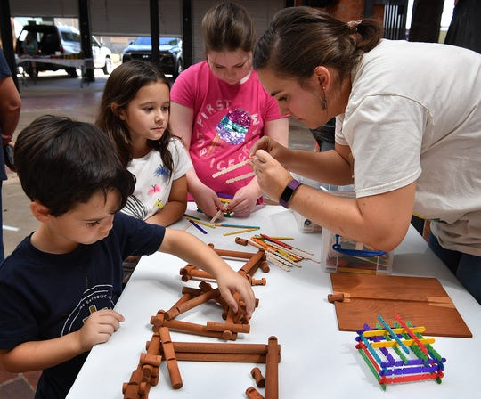 Madeleine Calcote, executive director of the Museum of North Texas History,  talks with Andrew, 5, Elizabeth, 8 and Emma McCartney, 10, about vintage construction toys during the Summer Kids Program at the Wichita Falls Farmers Market Tuesday.