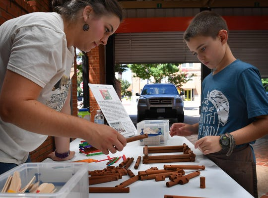 Caleb Simmons, 9,  and Museum of North Texas History Executive Director Madeleine Calcote work on a Lincoln Log cabin during the Summer Kids Program Tuesday morning at the Wichita Falls Farmers Market.