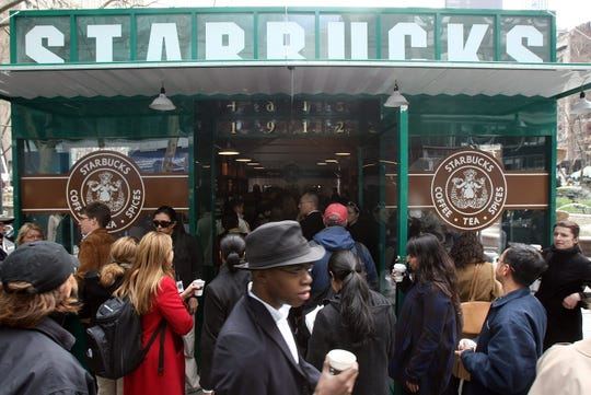 People gather at a replica of the original Seattle Pike Place Market Starbucks in Manhattan's Byant Park.