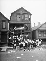 In this 1919 photo provided by the Chicago History Museum, a crowd gathers at a house that has been vandalized and looted during the race riots in Chicago.