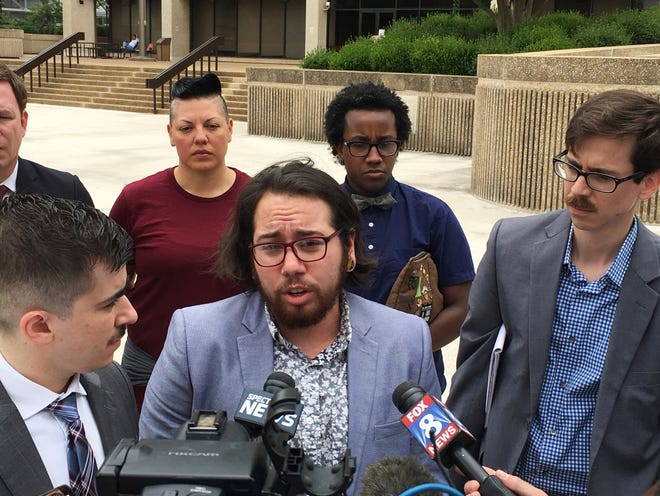"In a June 25, 2018 file photo, plaintiff Joaquin Carcano, center, addresses reporters after a hearing in Winston-Salem, N.C., on their lawsuit challenging the law that replaced North Carolina's ""bathroom bill.""  A federal judge approved a legal settlement Tuesday, July 23, 2019 affirming transgender people's right to use restrooms matching their gender identity in many North Carolina public buildings."