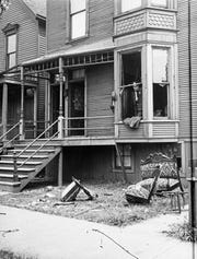 In this 1919 photo provided by the Chicago History Museum, police look through a broken window of a house during the race riots in Chicago.