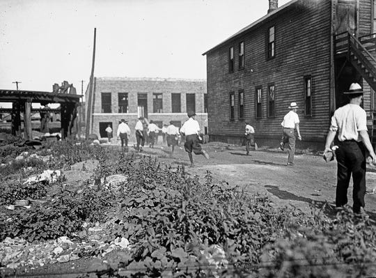 In this 1919 photo provided by the Chicago History Museum, a mob runs with bricks during the race riots in Chicago.
