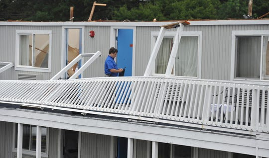 A Yarmouth building department worker surveys the damage to the second floor of the Cape Sands Inn where a tornado touched down ripping off the second floor of the structure, Tuesday, July 23, 2019, in West Yarmouth, Mass.