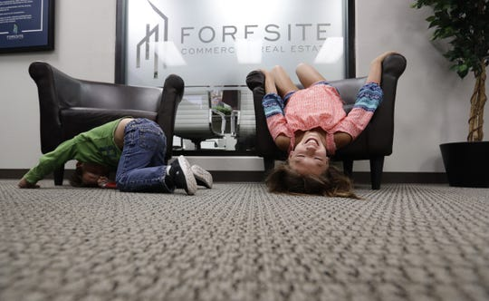 Ethan Babcock, left, and Baylee Parra, right, pass the time as each waits for a parent to finish in a meeting at Foresite Commercial Real Estate in San Antonio. Ethan Babcock's mom, Bethany Babcock, co-owner of Foresite Commercial Real Estate, has done things at the company like buy a plane ticket for a staffer who needed to visit a relative on life support and paid moving expenses for a staffer who was having family problems.
