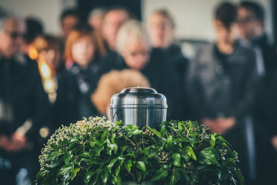 A metal urn with ashes of a dead person on a funeral, with people mourning in the background on a memorial service.