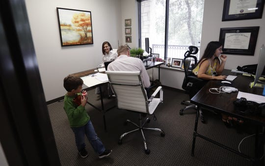 Bethany Babcock, co-owner of Foresite Commercial Real Estate, back left, talks with her son, Ethan, left, at her office in San Antonio.  For many small business owners, being a boss means helping staffers when they struggle Babcock, who runs a family friendly business, has bought a plane ticket for a staffer who needed to visit a relative on life support and paid moving expenses for a staffer who was having family problems, as well as permitting staff to bring their children to work.