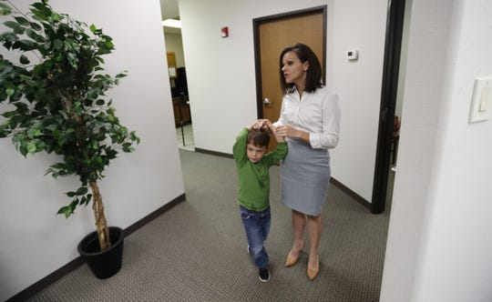 Bethany Babcock, co-owner of Foresite Commercial Real Estate, right, stands with her son, Ethan, at her office in San Antonio. For many small business owners, being a boss means helping staffers when they struggle Babcock, who runs a family friendly business, has bought a plane ticket for a staffer who needed to visit a relative on life support and paid moving expenses for a staffer who was having family problems, as well as permitting staff to bring their children to work.
