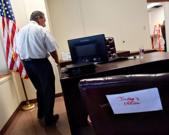 Taylor County Judge Downing Bolls walks to his desk inside his new office inside the 1915 Taylor County Courthouse. Bolls and other members of the Commissioners Court moved across the street Wednesday from the county courthouse.