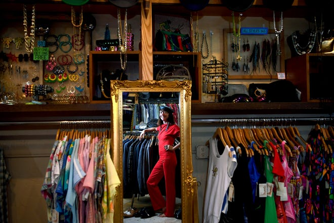 """Sara Legatski, owner of Honeypot Vintage Emporium in downtown Asheville, poses in a 1980s look from her store on July 24, 2019. Legatski sold about 300 pieces of clothing to outfit the cast and extras on the latest season of the Netflix show """"Stranger Things"""" which is set in the summer of 1985."""