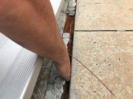Madison County Schools Maintenance Director Joe Davis reaches into cracked concrete to highlight the patchwork needed to remediate tripping hazards at the Madison High School athletics stadium.