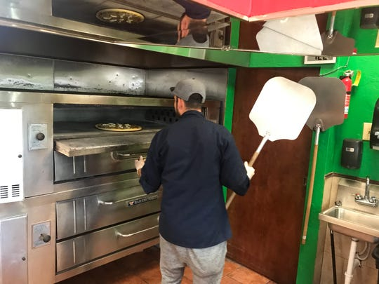 Jose Rodriguez, a co-manager of Hacienda Pizzeria, checks on a pizza while it bakes in the oven.
