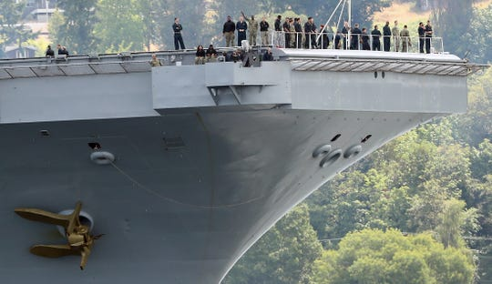 Sailors stand along the bow as the USS Nimitz passes Bachmann Park on its way to Naval Base Kitsap Bremerton on Wednesday, July 24, 2019.