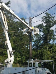 Crews work to attach wires to a new utility pole that supplies power to the PATCO Hi-Speedline. A downed pole had cut power to the Ashland and Lindenwold stations, keeping both closed since Monday.