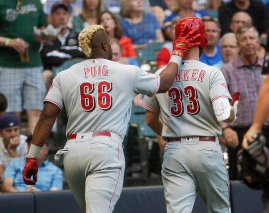 Cincinnati Reds' Yasiel Puig congratulates Jesse Winker (33) on his two-run home run during the first inning of a baseball game against the Milwaukee Brewers Tuesday, July 23, 2019, in Milwaukee.