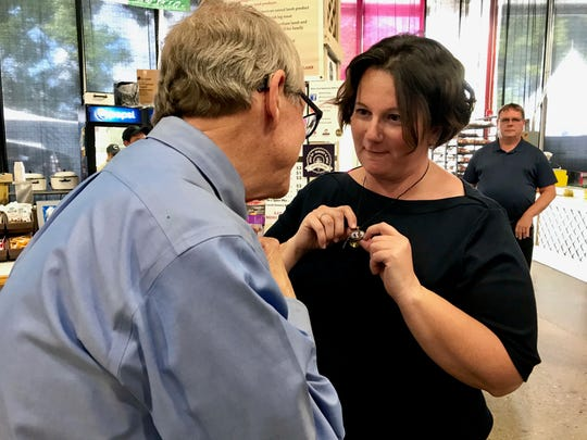 Amber Duffield of Columbus shows Gov. Mike DeWine the necklace she wears every day to remind her of her son, Tyler Jarrell, who died after a ride broke at the Ohio State Fair in 2017.