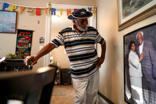 Marvin Porter, now in his second year without his wife Irene Porter, looks down at a photo he had printed and framed for his wall at the Porter household in Clarksville, Tenn., on Tuesday, July 23, 2019.