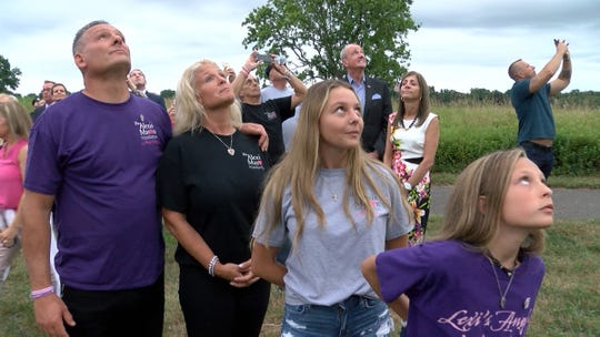 Rob and Denise Mason watch along with their daughters Brianna and Jessica as balloons launch during a dedication ceremony that was held to rename a trail at the Sunnyside Recreation Area in the Lincroft section of Middletown Tuesday evening, July 23, 2019, to honor Alexis 'Lexi' Mason.   She died unexpectedly at the age of 12 after going into cardiac arrest during a training run with the St. Mary's Soccer Club at the recreation area.