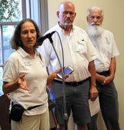 Judge Melanie Riggs of America in Bloom addresses a reception Tuesday at the Roscoe Village Visitors Center with Tim France of the local steering committee and partner judge Douglas Airhart looking on. Coshocton has competed in the national floral and landscape competition eight times.