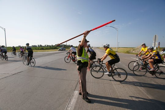 An Iowa state trooper directs traffic as RAGBRAI riders cross U.S. Highway 65 south of Indianola.