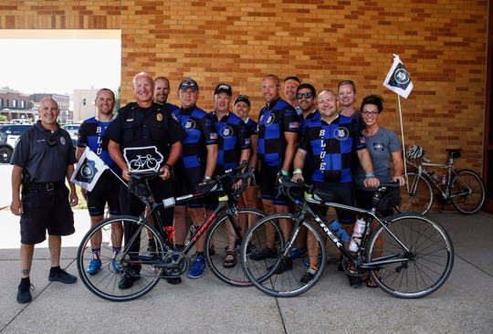 Members of Team Blue, headed by Sgt. Brad Kress of the Des Moines Police Dept., present the Indianola Police Department with an award during a ceremony at the Indianola police station during RAGBRAI on Tuesday, July 23, 2019.