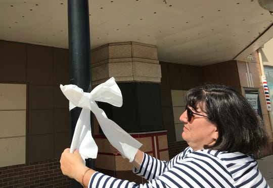Diane Brus of Berkley, whose son went to school with Tyler Wingate, puts up ribbons on 12 Mile in Berkley on Wednesday, July 24, 2019.