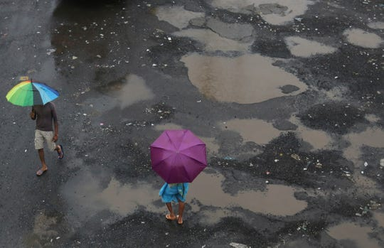 People walk with umbrellas in the rain in Mumbai, India, Wednesday, July 24, 2019. India's monsoon season runs from June to September.