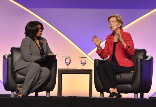 Presidential candidate Sen. Elizabeth Warren speaks Wednesday at the NAACP national convention in Detroit, answering questions from moderator April Ryan, left.