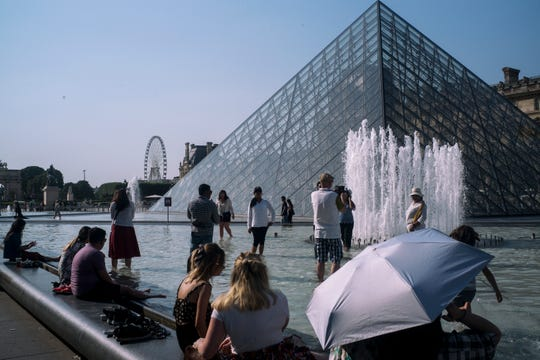 People cool off next to the fountains at Louvre Museum in Paris on Wednesday