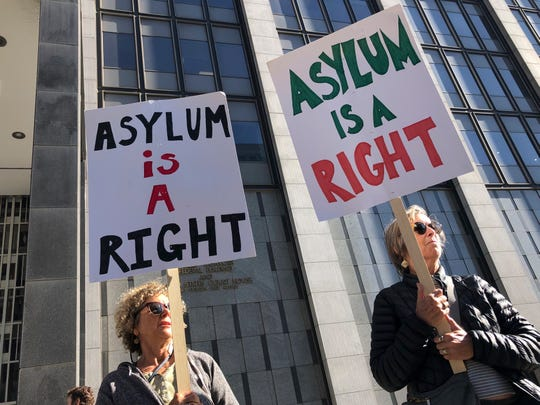 "Protestors hold signs that read "" Asylum is a Right"" outside of the San Francisco Federal Courthouse on Wednesday, July 24, 2019 in San Francisco, Calif. A federal judge said Wednesday that the Trump administration can enforce its new restrictions on asylum for people crossing the U.S.-Mexico border while lawsuits challenging the policy play out."