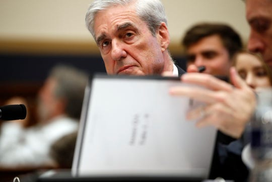 Former special counsel Robert Mueller, checks pages in the report as he testifies before the House Judiciary Committee hearing on his report on Russian election interference, on Capitol Hill, Wednesday, July 24, 2019 in Washington.