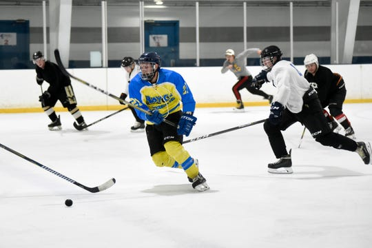Mike Kavlakian of Lapeer, middle, races to the puck during tryouts for the new Interstate Hockey League on July 13 at Fraser Hockeyland.
